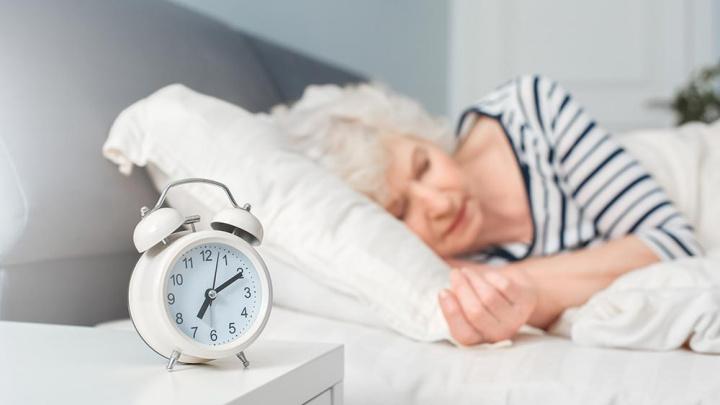 Alarm clock and senior lady sleeping - Senior Living Health Tips